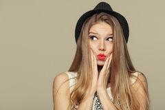 Surprised happy beautiful young woman looking up in excitement. Fashion girl in hat Stock Images