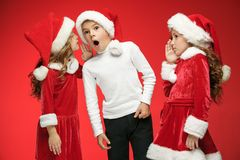 The happy boy and girls in santa claus hats with gift boxes at studio. The surprised and happy boy and girls in santa claus hats with gift boxes at red studio Royalty Free Stock Photos