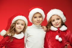 The happy boy and girls in santa claus hats with gift boxes at studio. The surprised and happy boy and girls in santa claus hats with gift boxes at red studio Stock Photography