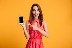 Surprised happy brunette woman in dress showing blank smartphone screen. And pointing at him while looking at the camera over yellow background stock image