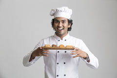 Surprised happy male chef holding cookies. A male chef enjoying fragrance of cookies on grey gradient background royalty free stock photography