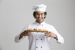 Surprised happy male chef holding cookies Stock Photography