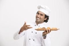 Surprised happy male chef showing cookies Royalty Free Stock Photo