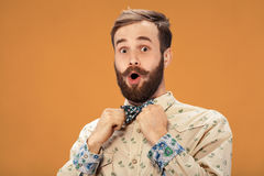 Surprised happy man with beard and moustache looking sideways in excitement,  on orange background Royalty Free Stock Images