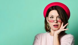 Surprised happy Pretty brunette woman in dress, felt hat and sunglasses holding arms on cheeks while looking at the camera stock photography