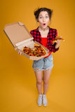 Surprised happy pretty young woman standing and holding pizza Stock Image