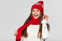 Surprised happy woman in excitement. Christmas girl wearing knitted warm hat and scarf, isolated on gray background.  stock photos
