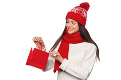 Surprised happy woman holding and looks in red bag in excitement, shopping. Christmas girl on winter sale with gift, isolated. On white background royalty free stock images