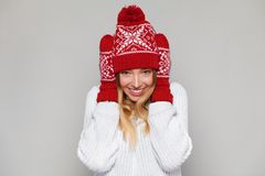 Surprised happy woman looking sideways in excitement. Christmas girl wearing knitted warm hat and mittens, isolated on gray backgr stock images