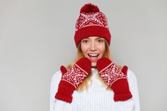 Surprised happy woman looking sideways in excitement. Christmas girl wearing knitted warm hat and mittens, isolated on gray backgr stock image