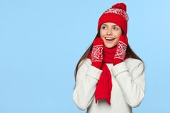Surprised happy woman looking sideways in excitement. Christmas girl wearing knitted warm hat and scarf, isolated on blue backgrou Stock Image