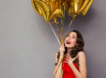 Surprised happy woman in red dress holding balloons Royalty Free Stock Photos