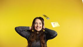 Surprised happy woman standing under money rain banknotes falling down. Success, business, and fortune concept. Slow motion stock footage