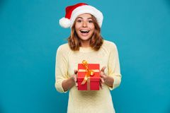 Surprised happy woman in sweater and christmas hat holding gift. Box and looking at the camera over blue background Stock Image