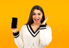 Surprised happy woman in white sweater showing a new smartphone. While looking at the camera with open mouth on yellow background royalty free stock images