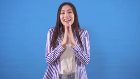 Surprised happy young asian woman on a blue background