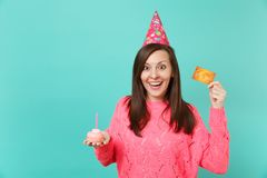 Surprised happy young woman in knitted pink sweater, birthday hat holding in hand cake with candle credit card isolated. On blue turquoise wall background royalty free stock images