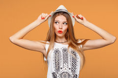 Surprised happy young woman looking sideways in excitement. Isolated over orange background stock photo