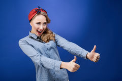 Surprised happy young woman showing thumbs up looking sideways i Royalty Free Stock Photography