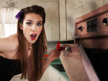 Surprised Housewife Checks the Oven. Surprised beautiful Caucasian housewife in kitchen checks her oven Royalty Free Stock Photo