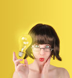 Surprised Idea Woman with Lightbulb. A woman is holding a light bulb and looks surprised. There is a yellow background with room for your text. The light bulb Stock Photo