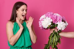 Surprised impressed young woman looking at bouquet with happiness, opening her mouth widely with shock, raising hands, wearing. Green dress. Unknown hand stock photos