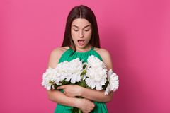 Indoor shot of shocked impressed young woman looking at bouquet with open mouth, stands embracng aring green dress. Unknown hand. Surprised impressed young woman royalty free stock image