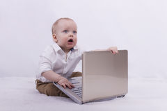 Surprised infant businessman with laptop. Cute toddler boy playing with notebook. Idea for extreme degree of surprise Stock Images