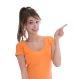 Surprised isolated young woman presenting with her finger. Royalty Free Stock Photos