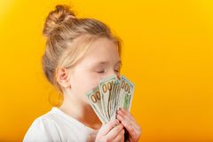 Surprised and joyful girl holds dollars in their hands and covers their face stock photos