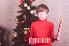 Surprised kid boy holding christmas gift in room Stock Photo