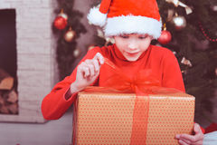 Surprised kid boy holding christmas gift in room Royalty Free Stock Photography