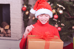 Surprised kid boy holding christmas gift in room Royalty Free Stock Images