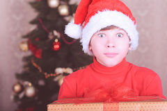 Surprised kid boy wearing santa hat over christmas lights Stock Photos