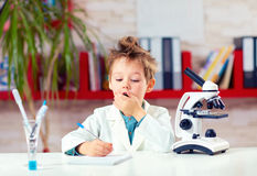 Surprised kid, boy writing notes after experiment in school lab Royalty Free Stock Image