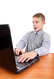 Surprised Kid with Laptop. Surprised Kid at the Desk with Laptop Isolated on the White Background royalty free stock photos