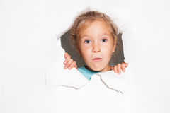 Surprised kid looking out of a hole in paper Stock Photo