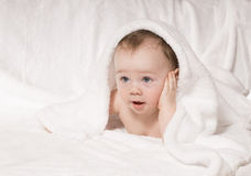 Surprised kid looks out from under a white blanket Royalty Free Stock Image