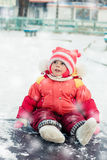 Surprised kid sitting on the ice in winter. Royalty Free Stock Photo