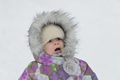 Surprised kid in warm clothes at winter snowy background Stock Photo