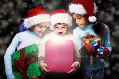 Surprised kids. In Santa hats looking inside the present box Royalty Free Stock Photo