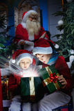 Surprised kids open the magic christmas gift Royalty Free Stock Photography
