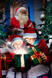 Surprised kids open the magic christmas gift Stock Photo