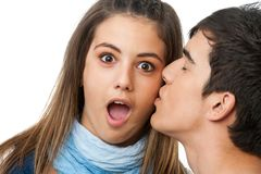 Surprised by kiss on cheek. Cute girl with surprised look and kiss on cheek .Isolated on white Royalty Free Stock Image