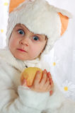 Surprised kitten. Little girl wearing a white kitten costume with an apple in her hands Royalty Free Stock Photography