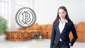 Surprised lächelnde junge Frau, die einen Anzug trägt und eine cryptocurrency Skizze auf einer flachen Wand des Designs betrachte Stockfotos