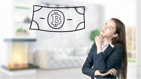 Surprised lächelnde junge Frau, die einen Anzug trägt und eine cryptocurrency Skizze auf einer flachen Wand des Designs betrachte Lizenzfreie Stockfotos