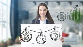 Surprised lächelnde junge Frau, die einen Anzug trägt und eine cryptocurrency Skizze auf einer flachen Wand des Designs betrachte Stockfoto