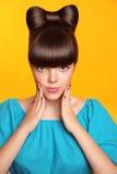 Surprised lächelndes jugendlich Mädchen mit Bogen Frisur, Make-up und colou Stockfotos