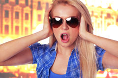 Surprised lady Holding her face in astonishm. Closeup portrait of surprised lady Holding her face in astonishment wearing sunglasses in the street Royalty Free Stock Image